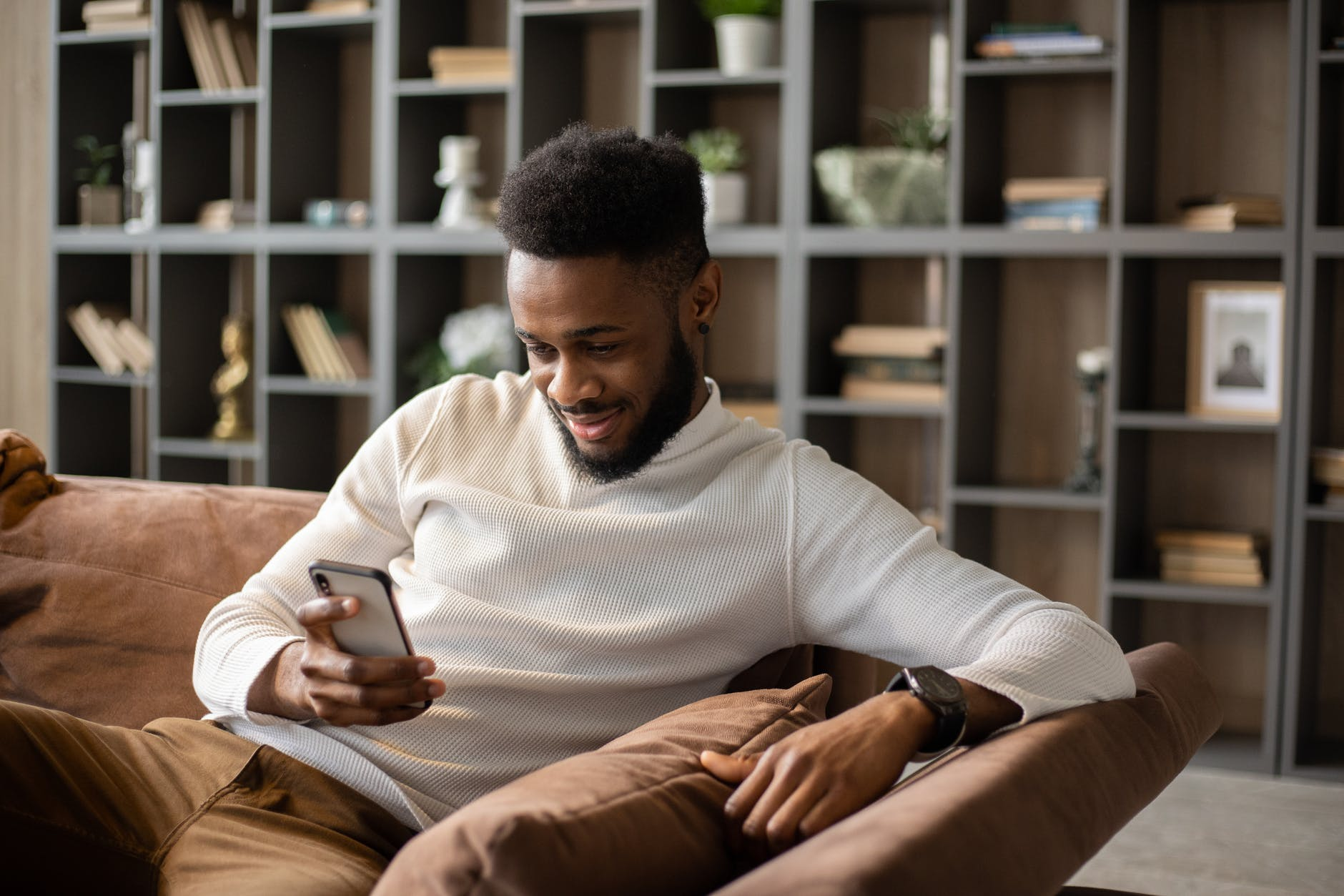 smiling young black man having video call at home
