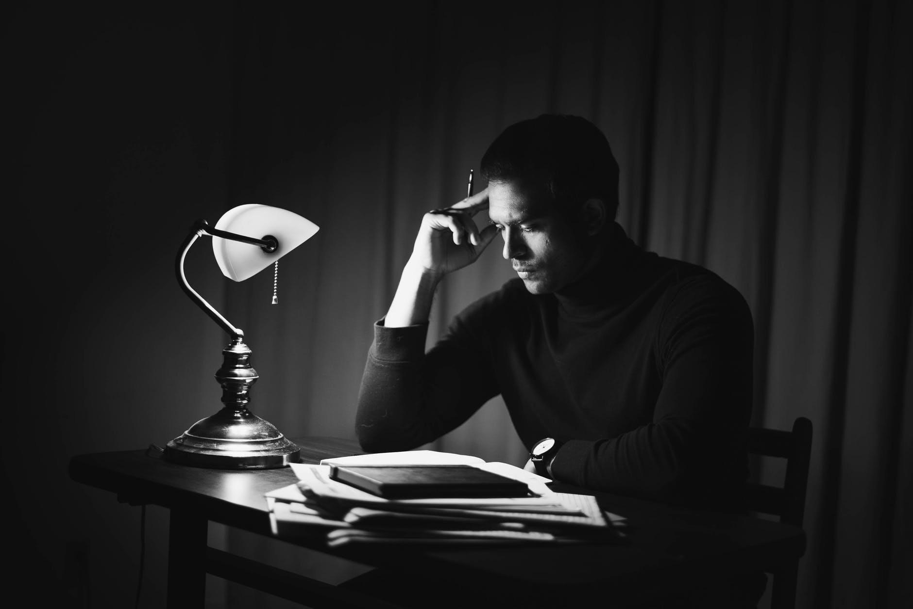 contemplative man reading book in classy home office