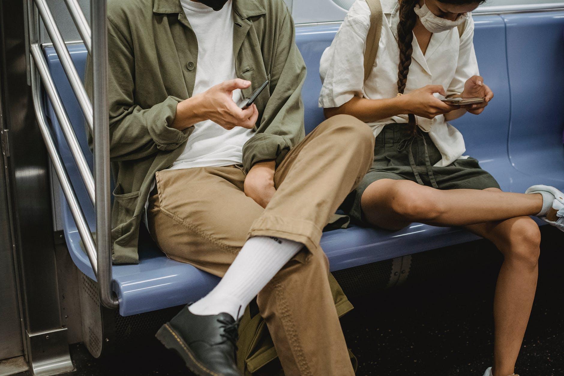 crop couple browsing smartphones in subway carriage