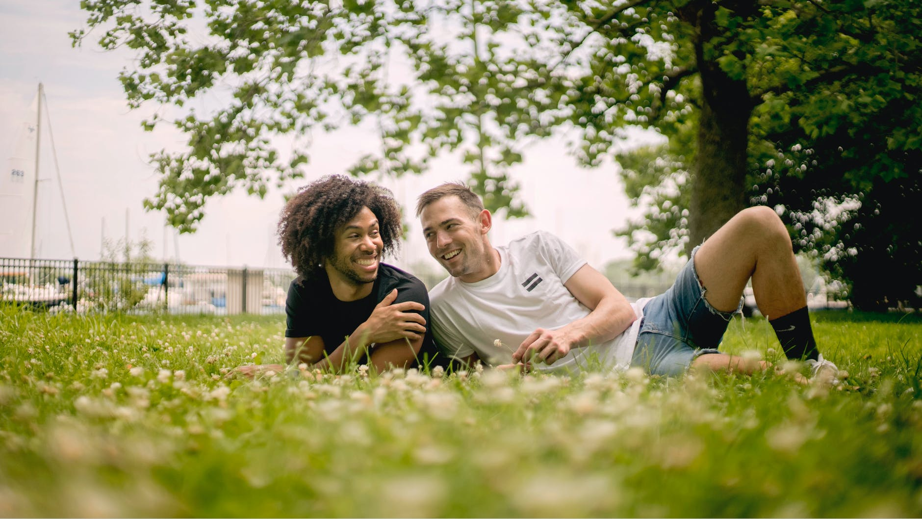 smiling men lying on grass